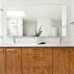 Mittelgroßes Modernes Badezimmer En Suite mit flächenbündigen Schrankfronten, hellbraunen Holzschränken, Duschnische, Toilette mit Aufsatzspülkasten, weißen Fliesen, Keramikfliesen, grauer Wandfarbe, Porzellan-Bodenfliesen, Unterbauwaschbecken, Quarzwerkstein-Waschtisch, beigem Boden, Falttür-Duschabtrennung und weißer Waschtischplatte in Portland