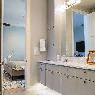 Imagen de cuarto de baño principal, contemporáneo, con armarios con paneles lisos, puertas de armario grises, baldosas y/o azulejos grises, baldosas y/o azulejos blancos, azulejos en listel, suelo vinílico, lavabo integrado y encimera de acrílico