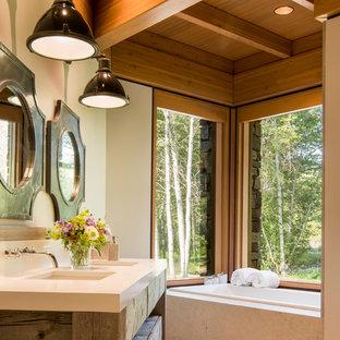 Imagen de cuarto de baño principal, rural, de tamaño medio, con armarios tipo mueble, puertas de armario de madera oscura, bañera encastrada, paredes beige, lavabo bajoencimera, encimera de cuarzo compacto y suelo beige