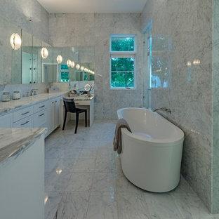 Diseño de cuarto de baño principal, actual, de tamaño medio, con armarios estilo shaker, puertas de armario grises, bañera exenta, ducha empotrada, baldosas y/o azulejos de piedra, paredes grises, suelo de mármol, lavabo bajoencimera y encimera de mármol