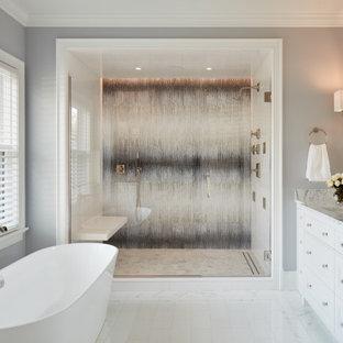 На фото: с высоким бюджетом большие главные ванные комнаты в стиле современная классика с фасадами островного типа, белыми фасадами, отдельно стоящей ванной, двойным душем, унитазом-моноблоком, белой плиткой, мраморной плиткой, серыми стенами, мраморным полом, врезной раковиной, мраморной столешницей и белым полом