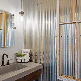 Inspiration for a large cottage concrete floor, brown floor and single-sink alcove shower remodel in Milwaukee with shaker cabinets, brown cabinets, a two-piece toilet, white walls, an undermount sink, quartz countertops, a hinged shower door, beige countertops and a freestanding vanity