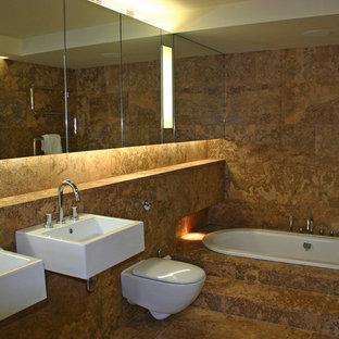 Ispirazione per una stanza da bagno padronale minimalista di medie dimensioni con lavabo sospeso, ante di vetro, top in marmo, vasca sottopiano, WC sospeso, pareti arancioni, pavimento in marmo e piastrelle marroni