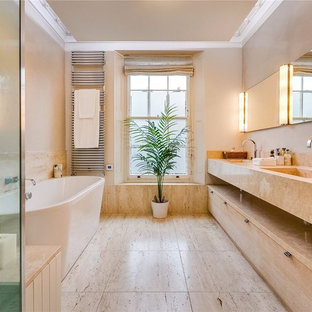This is an example of a medium sized mediterranean ensuite bathroom in London with a freestanding bath, flat-panel cabinets, orange cabinets, orange walls and an integrated sink.