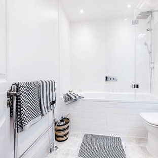 Design ideas for a small modern bathroom in Stockholm with a wall-mounted sink, freestanding cabinets, grey cabinets, a built-in bath, a one-piece toilet, white tiles, white walls, ceramic flooring and a shower/bath combination.