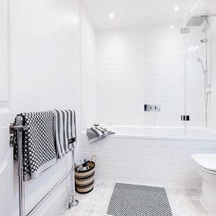 Diseño de cuarto de baño moderno, pequeño, con lavabo suspendido, armarios tipo mueble, puertas de armario grises, bañera encastrada, sanitario de una pieza, baldosas y/o azulejos blancos, paredes blancas, suelo de baldosas de cerámica y combinación de ducha y bañera