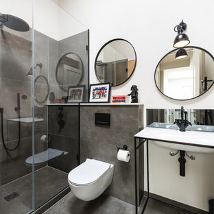 Medium sized industrial bathroom in London with a wall mounted toilet, grey tiles, white walls, a console sink, black floors and a sliding door.