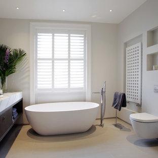 Imagen de cuarto de baño principal, contemporáneo, con lavabo integrado, armarios con paneles lisos, puertas de armario de madera en tonos medios, bañera exenta, sanitario de pared y paredes grises