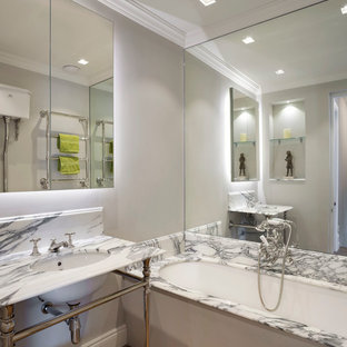 Inspiration for a small bohemian family bathroom in London with glass-front cabinets, white cabinets, a built-in bath, a shower/bath combination, beige tiles, mirror tiles, a built-in sink, marble worktops, multi-coloured worktops, a two-piece toilet, grey walls, medium hardwood flooring and grey floors.