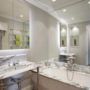 Ejemplo de cuarto de baño infantil, bohemio, pequeño, con armarios tipo vitrina, puertas de armario blancas, bañera encastrada, combinación de ducha y bañera, baldosas y/o azulejos beige, baldosas y/o azulejos con efecto espejo, lavabo encastrado, encimera de mármol, encimeras multicolor, sanitario de dos piezas, paredes grises, suelo de madera en tonos medios y suelo gris