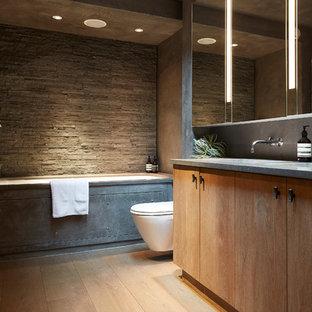 Mittelgroßes Modernes Badezimmer mit flächenbündigen Schrankfronten, hellen Holzschränken, Wandtoilette, grauen Fliesen, grauer Wandfarbe, hellem Holzboden, beigem Boden, grauer Waschtischplatte, Unterbauwanne, integriertem Waschbecken und Beton-Waschbecken/Waschtisch in London