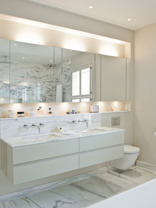 example of a trendy bathroom design in london with flat panel cabinets white cabinets