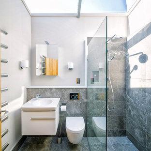 Пример оригинального дизайна: маленькая ванная комната в современном стиле с белыми фасадами, серой плиткой, полом из керамической плитки, плоскими фасадами, душем без бортиков, душевой кабиной, серыми стенами, инсталляцией, подвесной раковиной и открытым душем