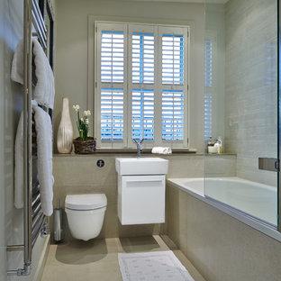 ロンドンの小さいモダンスタイルのおしゃれな浴室 (ドロップイン型浴槽、シャワー付き浴槽、壁掛け式トイレ、グレーのタイル、磁器タイル、グレーの壁、磁器タイルの床、珪岩の洗面台、壁付け型シンク) の写真