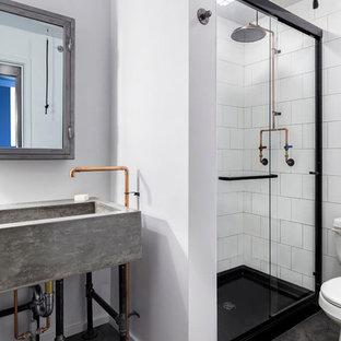 Immagine di una stanza da bagno industriale con doccia alcova, piastrelle bianche, piastrelle in ceramica, pareti bianche, pavimento in gres porcellanato, top in cemento, pavimento grigio e porta doccia scorrevole