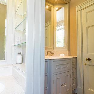 Idee per una stanza da bagno padronale tradizionale di medie dimensioni con lavabo da incasso, ante con bugna sagomata, ante verdi, top in pietra calcarea, vasca da incasso, WC monopezzo, pareti marroni e pavimento in pietra calcarea