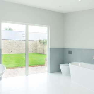 Country ensuite bathroom in Gloucestershire with a one-piece toilet, grey tiles, grey walls, a pedestal sink, white floors, a hinged door and a freestanding bath.