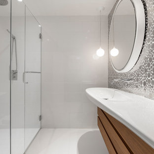 Photo of a small contemporary family bathroom with flat-panel cabinets, medium wood cabinets, a built-in shower, a one-piece toilet, white tiles, metal tiles, ceramic flooring, a wall-mounted sink, solid surface worktops, white floors and a hinged door.