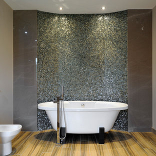 Inspiration for a contemporary ensuite bathroom in London with flat-panel cabinets, white cabinets, a freestanding bath, multi-coloured tiles, mosaic tiles and grey walls.