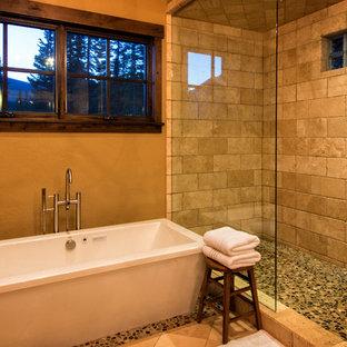 Rustik inredning av ett stort en-suite badrum, med ett fristående badkar, en dusch i en alkov, beige kakel, stenkakel, bruna väggar, klinkergolv i småsten och brunt golv