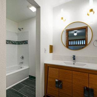 ポートランドのミッドセンチュリースタイルのおしゃれな浴室 (シャワー付き浴槽、分離型トイレ、白いタイル、サブウェイタイル、白い壁、磁器タイルの床、一体型シンク、大理石の洗面台、黒い床、白い洗面カウンター、独立型洗面台、中間色木目調キャビネット、ドロップイン型浴槽、シャワーカーテン、洗面台1つ) の写真
