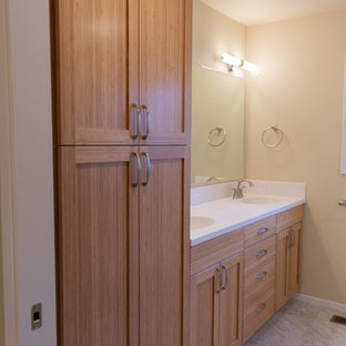 Example of a mid-sized trendy kids' linoleum floor and gray floor bathroom design in Other with shaker cabinets, medium tone wood cabinets, a two-piece toilet, beige walls, an integrated sink, solid surface countertops and beige countertops
