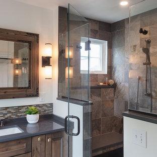 Идея дизайна: главная ванная комната среднего размера в стиле рустика с фасадами с выступающей филенкой, коричневыми фасадами, душем в нише, коричневой плиткой, плиткой из сланца, белыми стенами, врезной раковиной, столешницей из искусственного кварца, душем с распашными дверями и серой столешницей