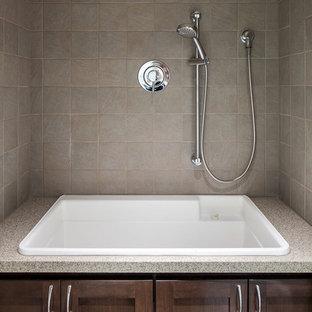 Immagine di una grande stanza da bagno moderna con ante in stile shaker, ante in legno bruno, top in quarzo composito, piastrelle grigie, piastrelle in gres porcellanato, pareti beige e pavimento in linoleum