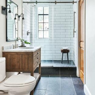 Esempio di una stanza da bagno con doccia mediterranea con consolle stile comò, ante in legno scuro, doccia ad angolo, WC monopezzo, piastrelle bianche, pareti beige, lavabo sottopiano, pavimento blu, porta doccia scorrevole e top bianco