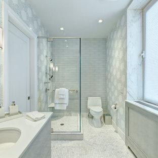 Modelo de cuarto de baño principal, tradicional renovado, grande, con armarios con paneles lisos, puertas de armario grises, ducha esquinera, sanitario de dos piezas, baldosas y/o azulejos grises, baldosas y/o azulejos blancos, baldosas y/o azulejos en mosaico, paredes grises, suelo con mosaicos de baldosas, lavabo bajoencimera y encimera de cuarcita