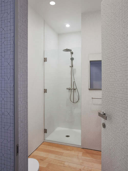Contemporary light wood floor alcove shower idea in New York