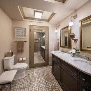 Modelo de cuarto de baño tradicional con armarios con paneles empotrados, puertas de armario negras, paredes beige, suelo con mosaicos de baldosas, lavabo bajoencimera, suelo beige y encimeras blancas