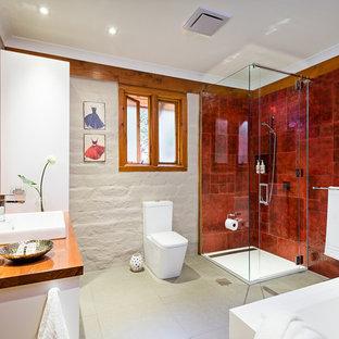 Diseño de cuarto de baño principal, rústico, de tamaño medio, con puertas de armario blancas, encimera de madera, ducha esquinera, sanitario de una pieza, baldosas y/o azulejos rojos, baldosas y/o azulejos de cerámica, paredes rojas y suelo de baldosas de cerámica