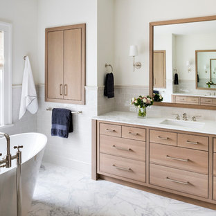 Example of a transitional master gray tile and subway tile freestanding bathtub design in New York with beaded inset cabinets, light wood cabinets, beige walls and an undermount sink