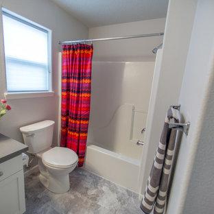 Esempio di una piccola stanza da bagno con doccia chic con ante in stile shaker, ante bianche, vasca ad alcova, doccia alcova, WC a due pezzi, pareti grigie, pavimento in laminato, top in granito, lavabo sottopiano, pavimento grigio e doccia con tenda