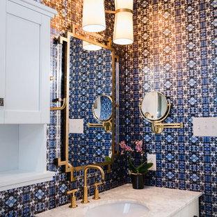 Cette image montre une petit salle de bain traditionnelle avec un placard à porte shaker, des portes de placard blanches, un mur bleu, un plan de toilette en quartz modifié, un plan de toilette blanc et un lavabo encastré.