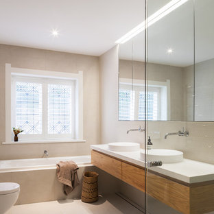 Design ideas for a mid-sized contemporary kids bathroom in Sydney with medium wood cabinets, beige tile, beige walls, beige floor, furniture-like cabinets, a wall-mount toilet, mosaic tile, a pedestal sink and wood benchtops.
