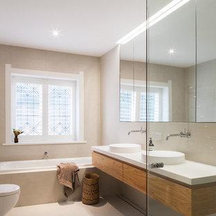 Diseño de cuarto de baño infantil, actual, de tamaño medio, con puertas de armario de madera oscura, baldosas y/o azulejos beige, paredes beige, suelo beige, armarios tipo mueble, sanitario de pared, baldosas y/o azulejos en mosaico, lavabo con pedestal y encimera de madera