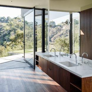 Imagen de cuarto de baño minimalista con armarios con paneles lisos, puertas de armario de madera oscura, paredes blancas, suelo de madera en tonos medios, lavabo bajoencimera, suelo marrón y encimeras blancas