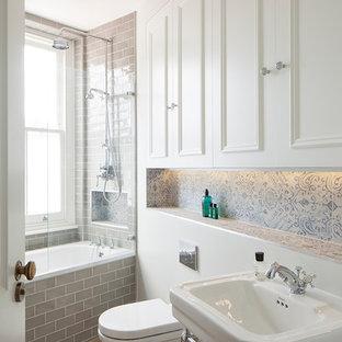 Klassisches Badezimmer mit Waschtischkonsole, weißen Schränken, Einbaubadewanne, Duschbadewanne, Porzellanfliesen, braunem Holzboden, Wandtoilette und Schrankfronten mit vertiefter Füllung in London