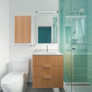 Ispirazione per una stanza da bagno design con lavabo sottopiano, ante lisce, doccia alcova, WC monopezzo, piastrelle blu, piastrelle di vetro e ante in legno chiaro