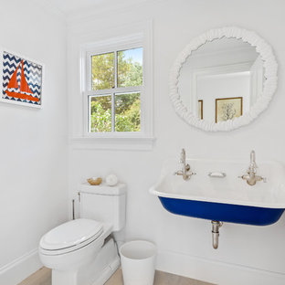 Beach style kids' light wood floor and beige floor bathroom photo in New York with a one-piece toilet, white walls and a trough sink