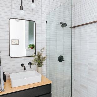 Immagine di una stanza da bagno con doccia nordica con ante lisce, ante nere, doccia alcova, piastrelle bianche, pareti bianche, lavabo a bacinella, top in legno, pavimento multicolore e doccia aperta