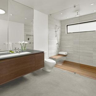 Modelo de cuarto de baño principal, moderno, de tamaño medio, con armarios con paneles lisos, puertas de armario de madera en tonos medios, ducha a ras de suelo, sanitario de una pieza, baldosas y/o azulejos grises, paredes blancas, suelo de cemento y lavabo bajoencimera