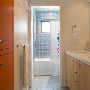 Réalisation d'une salle de bain vintage de taille moyenne pour enfant avec un lavabo encastré, un placard à porte plane, des portes de placard en bois clair, un plan de toilette en surface solide, une baignoire en alcôve, un WC à poser, un carrelage bleu, des carreaux de céramique, un mur blanc et un sol en carrelage de céramique.