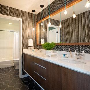 Ejemplo de cuarto de baño papel pintado, actual, papel pintado, con armarios con paneles lisos, puertas de armario de madera en tonos medios, paredes negras, lavabo bajoencimera, suelo negro, encimeras blancas y papel pintado
