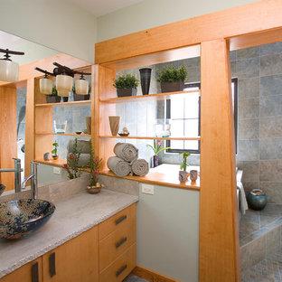 Ejemplo de cuarto de baño de estilo zen con lavabo sobreencimera, armarios con paneles lisos, puertas de armario de madera oscura, bañera empotrada y encimeras grises