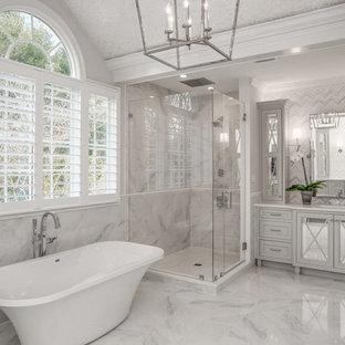 Идея дизайна: большая главная ванная комната в стиле современная классика с стеклянными фасадами, серыми фасадами, отдельно стоящей ванной, угловым душем, белой плиткой, мраморной плиткой, мраморной столешницей, белыми стенами, мраморным полом и врезной раковиной