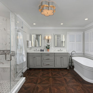 Inspiration for a timeless white tile and marble tile wood-look tile floor, brown floor, double-sink and wall paneling bathroom remodel in DC Metro with gray cabinets, gray walls, an undermount sink, quartz countertops, a hinged shower door, white countertops, raised-panel cabinets and a built-in vanity