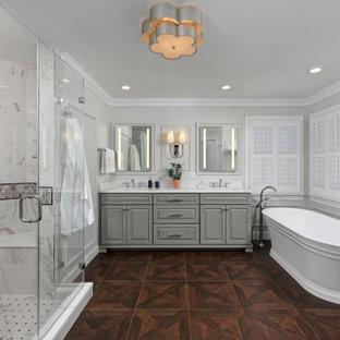 Cette photo montre une salle de bain chic avec des portes de placard grises, une baignoire indépendante, une douche d'angle, un carrelage blanc, du carrelage en marbre, un mur gris, un sol en carrelage imitation parquet, un lavabo encastré, un plan de toilette en quartz modifié, un sol marron, une cabine de douche à porte battante, un plan de toilette blanc, un banc de douche, meuble double vasque, un placard avec porte à panneau surélevé, meuble-lavabo encastré et du lambris.